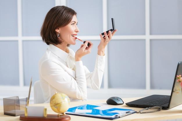 사무실에서 립 메이크업을 하 고 매력적인 비즈니스 우먼