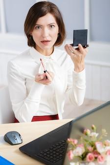 사무실에서 화장을 하 고 매력적인 비즈니스 우먼