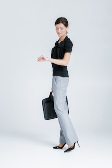 Привлекательная деловая женщина, держащая папку с документами и смотрящая на часы на