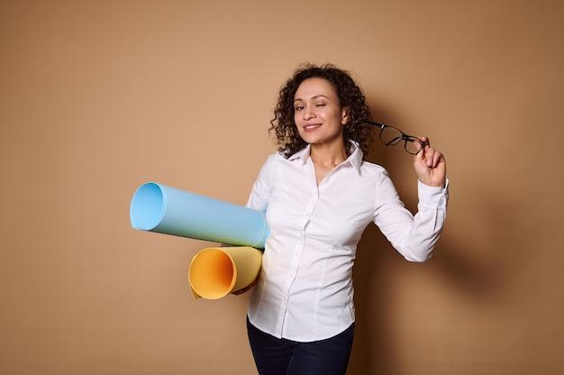コピースペースでベージュの壁にポーズをとってデザイン色画用紙を保持している魅力的なビジネス女性。