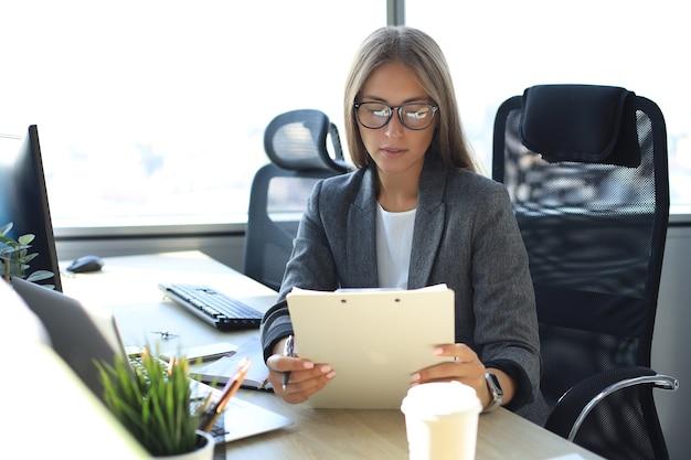 Привлекательная деловая женщина, держащая документы и смотрящая на них, сидя за столом в офисе.