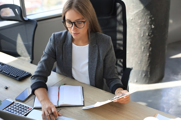 Attractive business woman holding documents and looking at them while sitting at the desk in office.