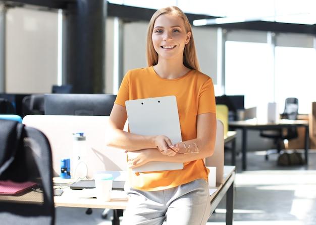 Привлекательная деловая женщина в элегантной повседневной одежде, глядя на камеру и улыбаясь, стоя в офисе.