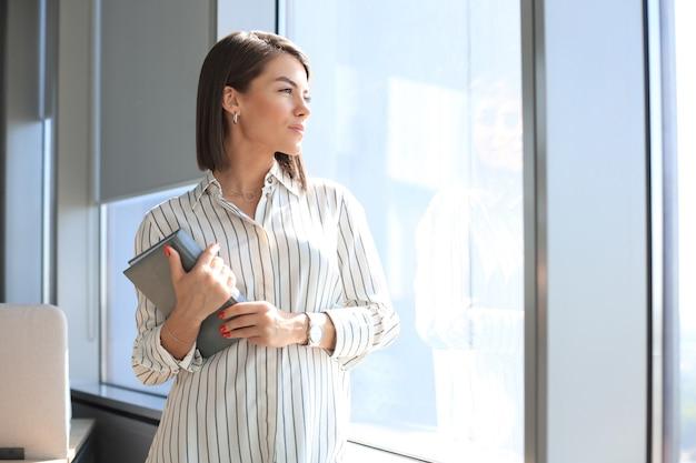 Привлекательная деловая женщина в элегантной повседневной одежде, глядя в сторону и улыбаясь, стоя в офисе.