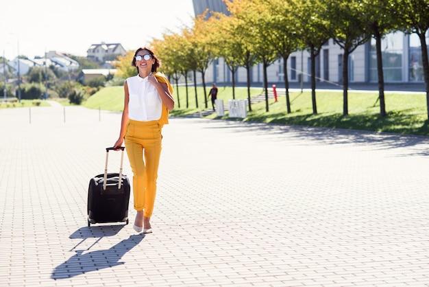 Привлекательная деловая женщина в стильном желтом костюме тянет чемодан, спешит в аэропорт. привлекательный бизнес женщина собирается в командировку, потянув ее чемодан за ней.