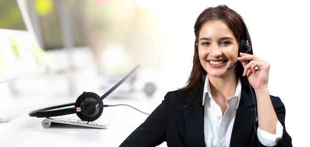 작업하는 동안 웃고 있는 양복과 헤드셋을 입은 매력적인 비즈니스 여성. 고객 서비스