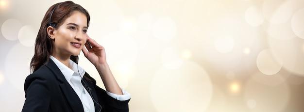 정장과 헤드셋을 입은 매력적인 비즈니스 여성이 일하는 동안 웃고 있습니다.