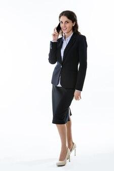 매력적인 비즈니스 우먼이 서서 전화로 말하고 웃고 있다