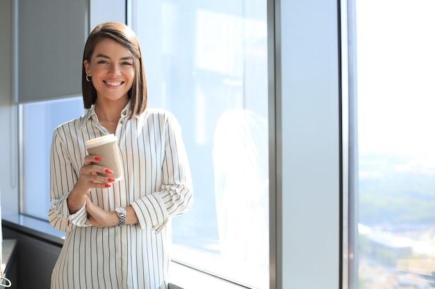 Привлекательная деловая женщина смотрит в камеру и улыбается, стоя в офисе.