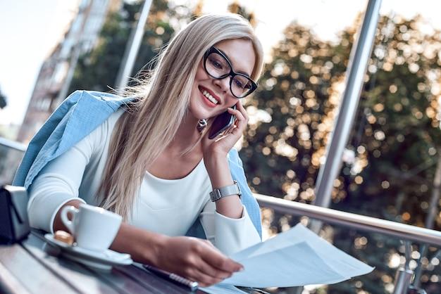 Привлекательная деловая женщина, читающая газеты в городском кафе