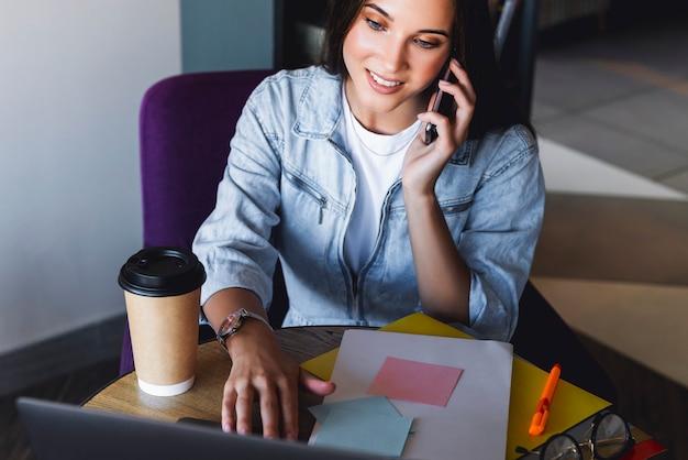 Привлекательная деловая женщина сидит за столом перед ноутбуком и разговаривает по мобильному телефону, ведет переговоры по телефону.