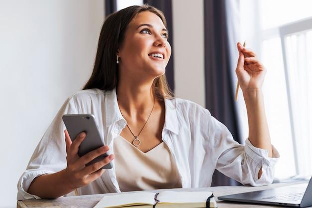 魅力的なビジネスウーマンがノートパソコンの前のテーブルに座って携帯電話で話し、電話で交渉します。
