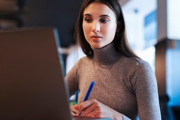 Привлекательная деловая женщина сидит за столом перед ноутбуком, делает заметки в блокноте, составляет график работы.