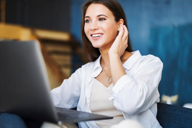 魅力的なビジネス女性はラップトップのテーブルに座って、スマートフォンはテーブルの上に横たわって、ノートに鉛筆でメモを作成します。