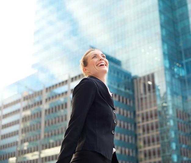 都市で笑顔と歩く魅力的なビジネス女性