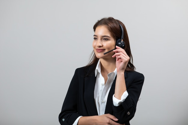 Attractive business woman in suits and headsets are smiling while working isolate