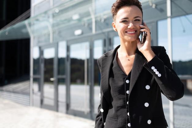 Привлекательная деловая женщина разговаривает по телефону возле офисного здания