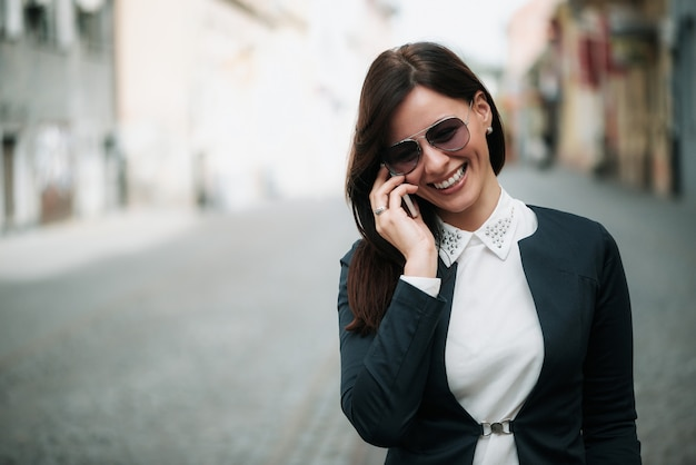Attractive business woman walking and talking on mobile phone in a city street.