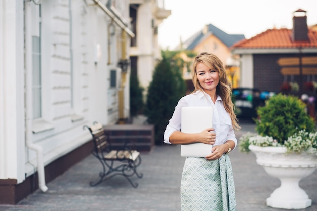 ノートパソコンで通りを歩いて長い髪を持つ魅力的なビジネス女性。彼女は白いシャツを着ています