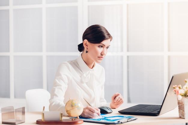 사무실에서 책상에서 일하는 매력적인 비즈니스 우먼