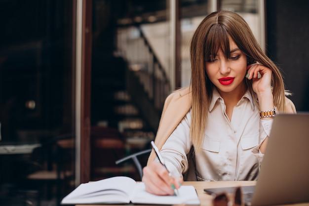 Привлекательная деловая женщина, работающая на компьютере в кафе