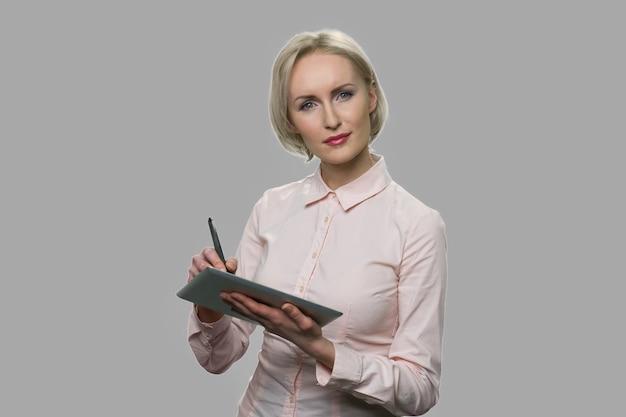 Привлекательная бизнес-леди работая на цифровом tabet. довольно среднего возраста бизнес-леди, опираясь на планшетный пк на сером фоне.