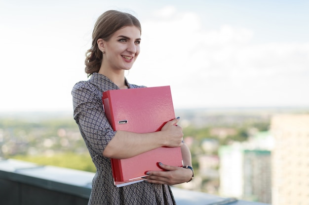 Attractive businesslady in patterned dress stand on the roof and hold paper folder