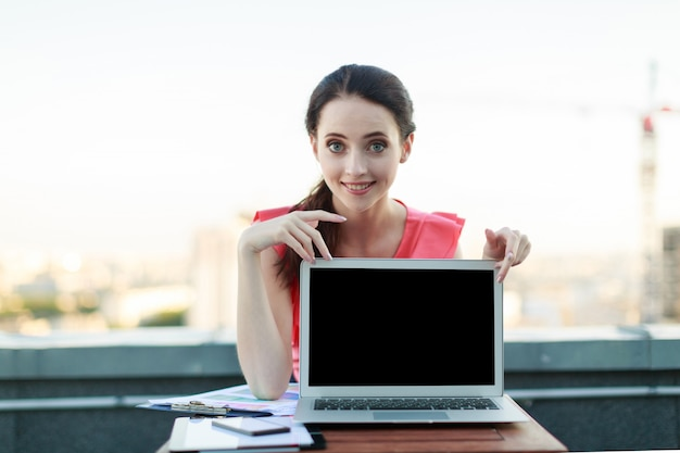 Attractive businesslady in pink blouse sit on the roof and work with laptop, show empty laptop