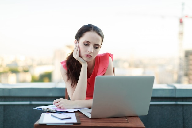 Attractive businesslady in pink blouse sit on the roof and work with laptop