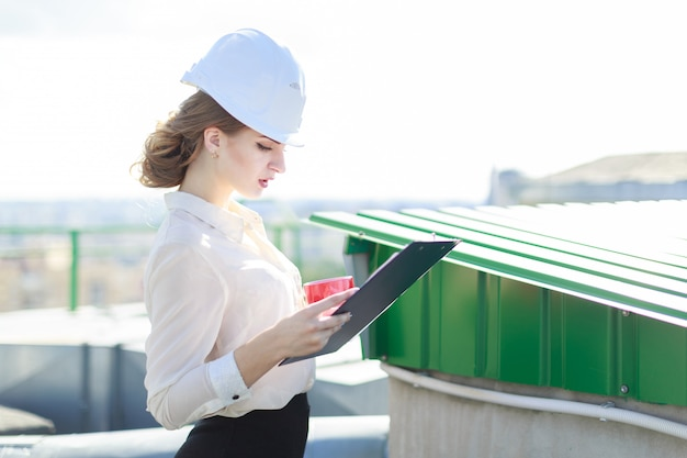 Attractive businesslady in white blouse, watch, helmet and black skirt stand on the roof and hold tablet and cup of coffe