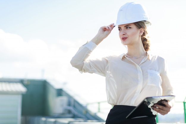 Attractive businesslady in white blouse, watch, helmet and black skirt stand on the roof and hold tablet