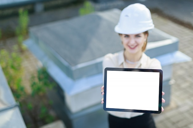 Attractive businesslady in white blouse, watch, helmet and black skirt stand on the roof and show empty tablet