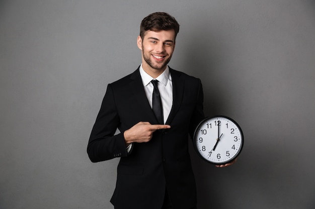 Attractive businessman in classic black suit pointing with finger on big clock,