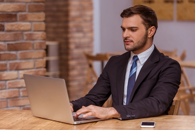 Attractive businessman in classical suit using a laptop.