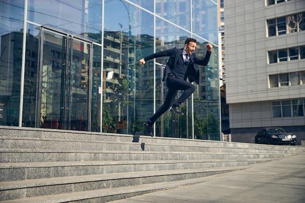 大きなガラスのビジネスセンターを出て急いで外に飛び出し、喜びで跳び上がる魅力的なビジネスマン Premium写真