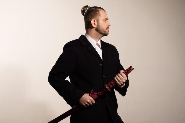 Привлекательный бизнесмен в черном костюме получает самурайский меч