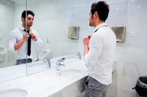 Привлекательный бизнесмен, глядя на себя в зеркало