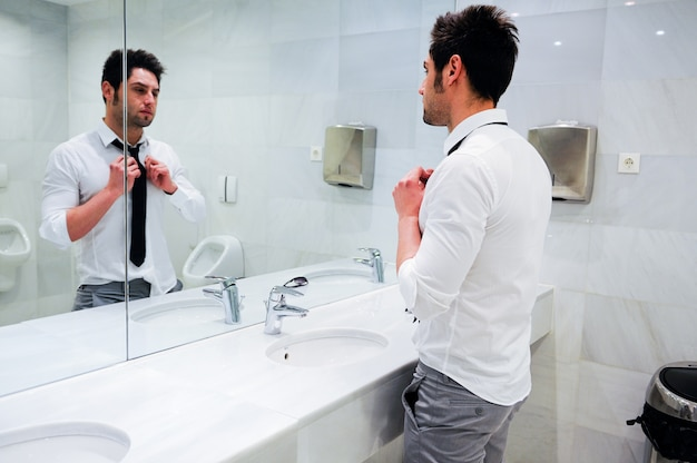 Attractive businessman looking at himself in the mirror