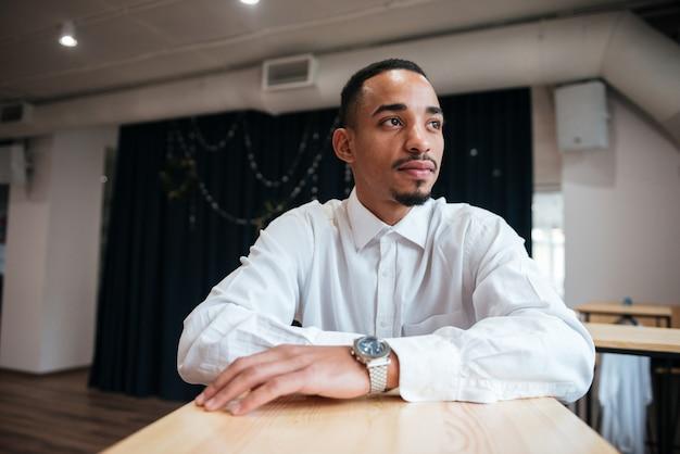 Привлекательный бизнесмен сидит за столом и смотрит в сторону