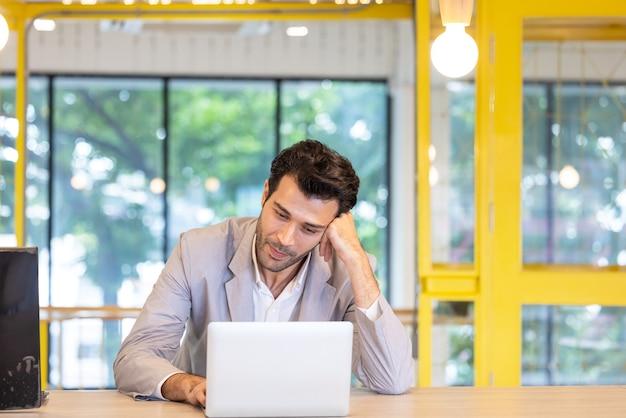 Привлекательный бизнесмен с помощью ноутбука в своем офисе открытого пространства