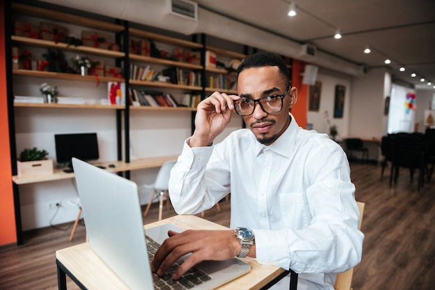 Attractive businessman wearing glasses sitting at the table typing by laptop computer