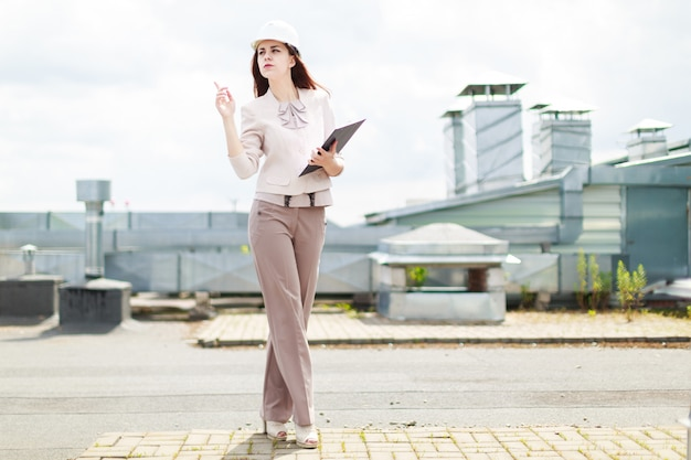 Attractive businesswoman in beige suit stand on the roof and hold tablet