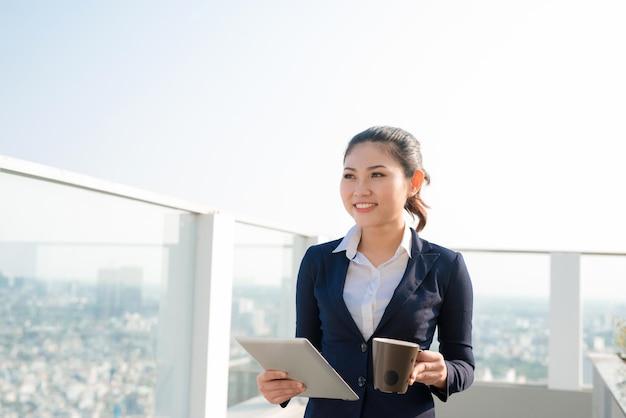 Привлекательная деловая женщина пьет кофе и использует цифровой планшет, стоя на улице и глядя на город