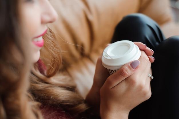 Привлекательная деловая женщина пьет кофе у окна