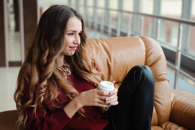 Привлекательная деловая женщина пьет кофе на диване