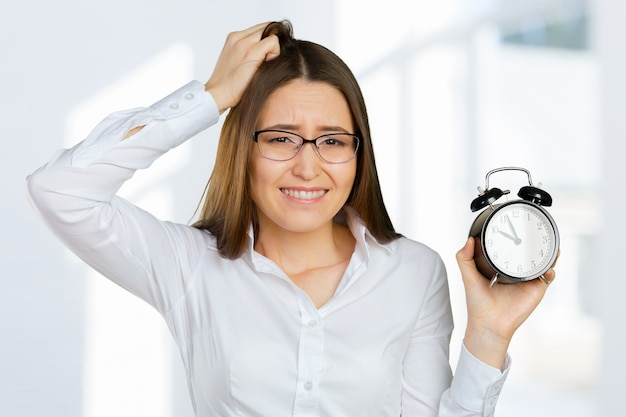 Attractive businesswoman holding alarm clock