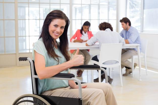 車椅子の魅力的な実業家はカメラに親指を与える