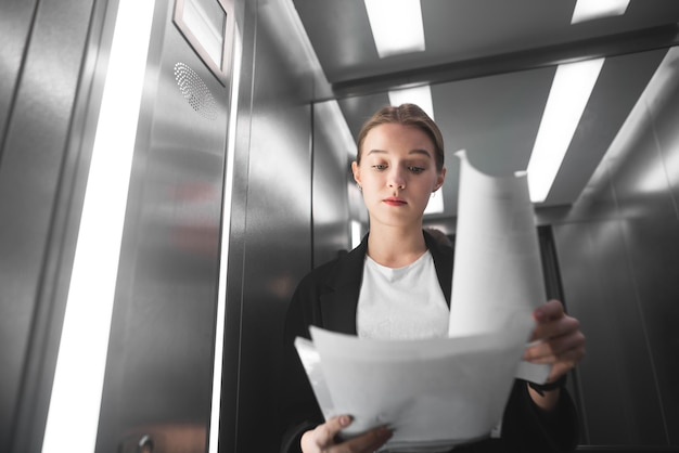 Симпатичная бизнесвумен скептически проверяет документацию в лифте.