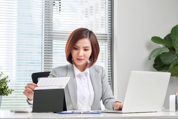 魅力的な実業家は、オフィスでコンピューターとカレンダーを持って机に座っています。