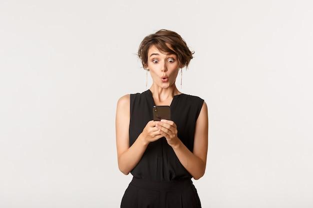 Привлекательная деловая женщина смотрит удивлен смартфон, стоя с мобильным телефоном над белой.